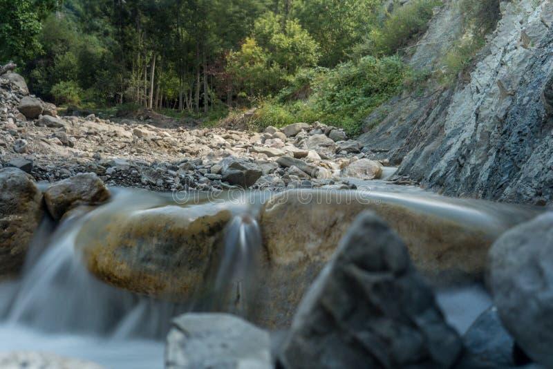 Ποταμός βουνών με το γρήγορο ρεύμα και με τα φωτεινά θολωμένα κύματα Μεγάλοι mossy λίθοι στο σαφές νερό στοκ εικόνες
