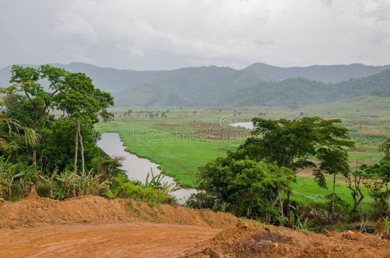 Ποταμός και βρώμικος δρόμος με τα βουνά και πολύβλαστη βλάστηση στην περιφερειακή οδό στο Καμερούν, Αφρική στοκ εικόνες