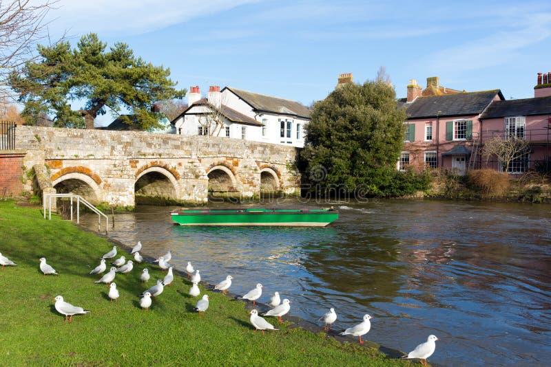 Ποταμός Avon Christchurch Dorset Αγγλία UK με τη γέφυρα και την πράσινη βάρκα στοκ εικόνες