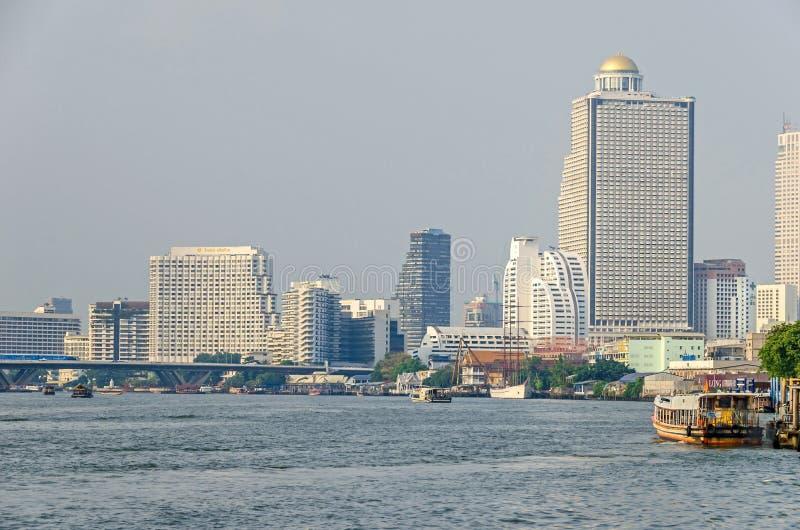 Ποταμός Phraya Chao με τις βάρκες, τη γέφυρα Taksin, τον πύργο πολύτιμων λίθων, τον κρατικό πύργο και το shangri-Λα στη Μπανγκόκ στοκ εικόνα με δικαίωμα ελεύθερης χρήσης