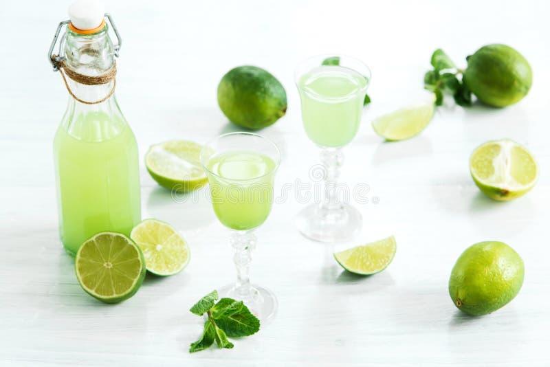 Ποτό εγχώριου ασβέστη σε ένα γυαλί και φρέσκα λεμόνια και ασβέστες στο άσπρο ξύλινο υπόβαθρο στοκ εικόνα