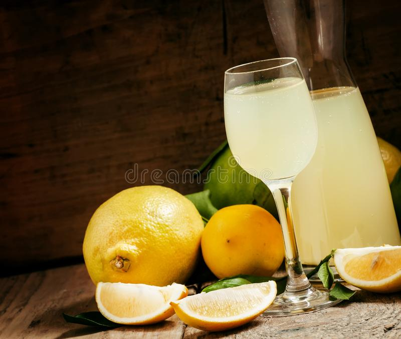 Ποτό εγχώριων λεμονιών, ηδύποτο λεμονιών σε ένα γυαλί και φρέσκα λεμόνια και στοκ εικόνες