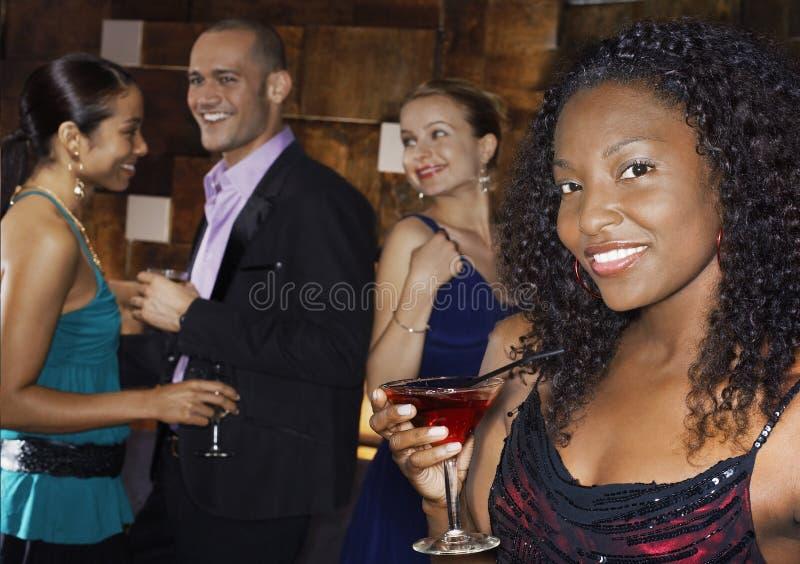 Ποτό εκμετάλλευσης γυναικών με τους ανθρώπους στο φραγμό στοκ εικόνα με δικαίωμα ελεύθερης χρήσης