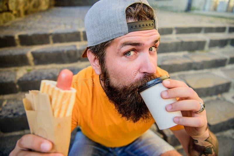 Ποτό κάτι διαφορετικό Το καυκάσιο hipster απολαμβάνει το take-$l*away ποτό με το χοτ-ντογκ Γενειοφόρο άτομο που παίρνει μια γουλι στοκ εικόνες με δικαίωμα ελεύθερης χρήσης