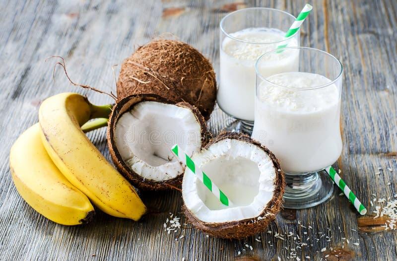 Ποτό καταφερτζήδων γάλακτος καρύδων με τις μπανάνες στο ξύλινο υπόβαθρο στοκ φωτογραφία