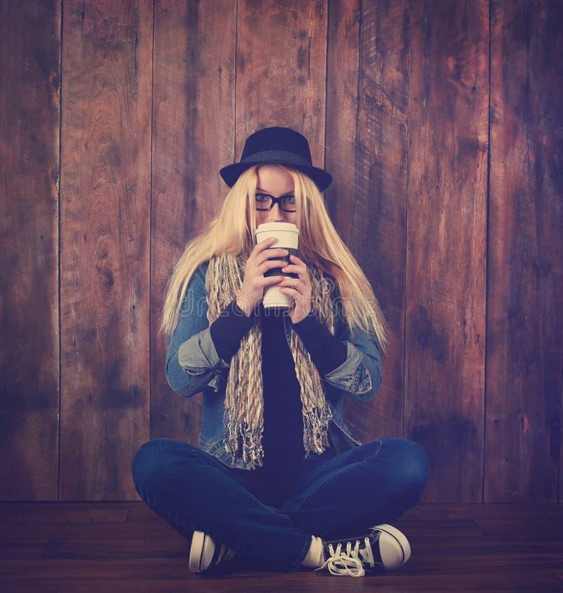 Ποτό καφέ κατανάλωσης γυναικών Hipster στο ξύλο στοκ εικόνα με δικαίωμα ελεύθερης χρήσης