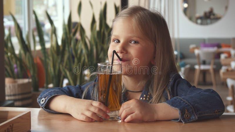 Ποτό μικρών κοριτσιών κάποιο αρωματικό νερό στον καφέ στοκ εικόνες