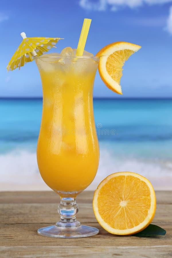 Ποτό φρούτων χυμού από πορτοκάλι στην παραλία στοκ φωτογραφία