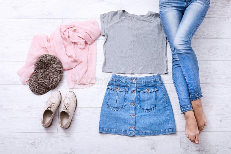 Πουκάμισο προτύπων Σύγχρονη εξάρτηση με τα διαφορετικά εξαρτήματα και τα θηλυκά πόδια στα τζιν στο άσπρο ξύλινο πάτωμα Τοπ διάστη στοκ φωτογραφία