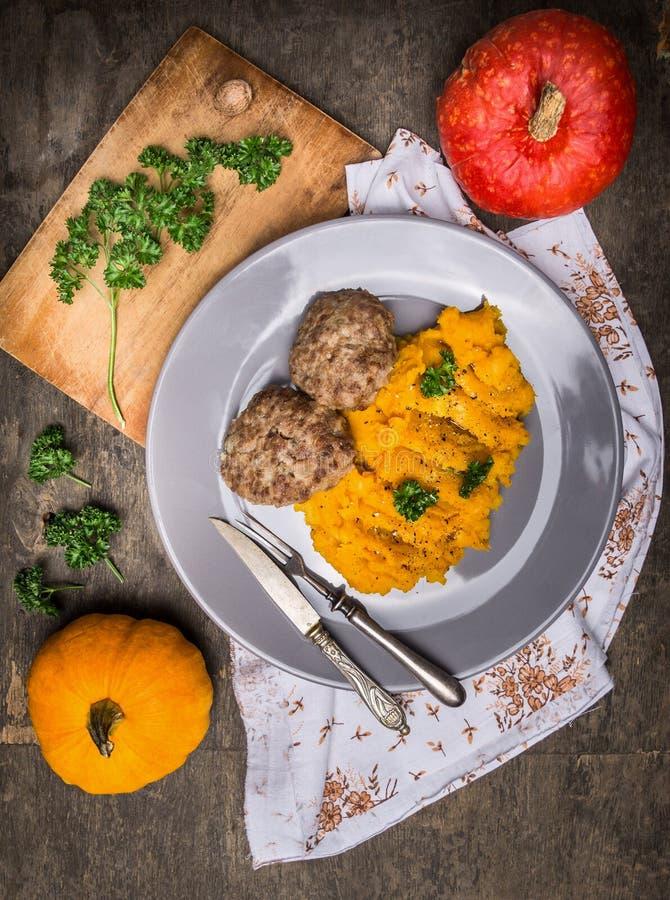Πουρές κολοκύθας με patties κρέατος στο πιάτο στον παλαιό ξύλινο πίνακα στοκ φωτογραφίες