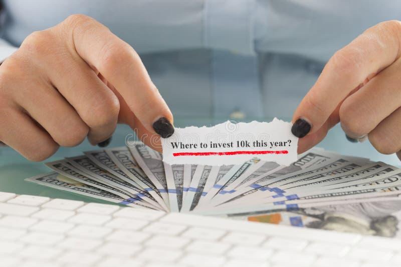 Πού να επενδυθεί 10k εξετάστε φέτος γραπτός στο μικρό κομμάτι χαρτί στο χέρι woman's επάνω από την αποταμίευση μετρητών σε αμερ στοκ εικόνες με δικαίωμα ελεύθερης χρήσης