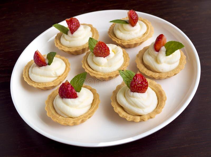 Πολλά κέικ, cupcakes με τους νωπούς καρπούς (φράουλες), την κτυπημένες κρέμα και τις μέντες στοκ εικόνες