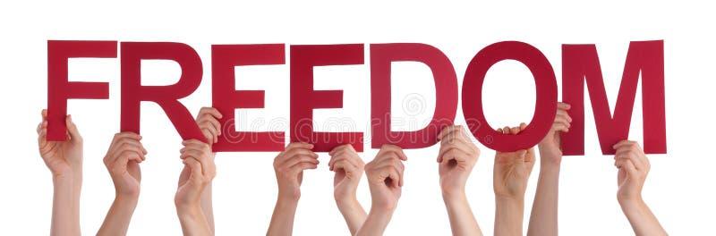 Πολλά χέρια ανθρώπων κρατούν την κόκκινη ευθεία ελευθερία του Word στοκ εικόνα