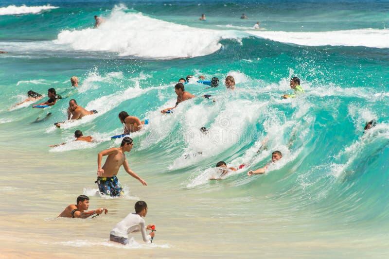 Πολλά bodysurfers σε ένα μεγάλο κύμα στην αμμώδη παραλία στοκ εικόνες