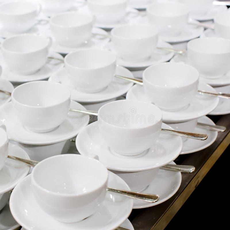 Πολλές σειρές του καθαρών άσπρων φλυτζανιού και του πιατακιού που σχεδιάζονται εκλεκτής ποιότητας σε αναδρομικό στοκ εικόνες με δικαίωμα ελεύθερης χρήσης
