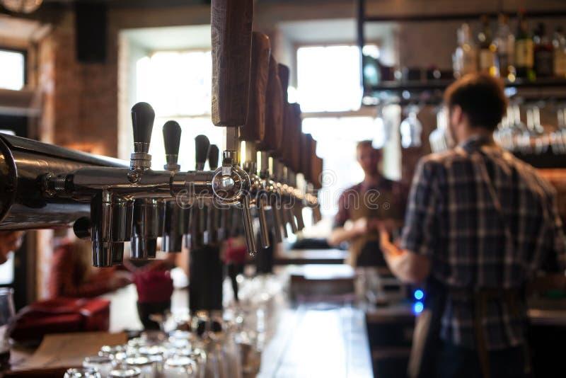 Πολλές χρυσές βρύσες μπύρας στο φραγμό στοκ φωτογραφίες