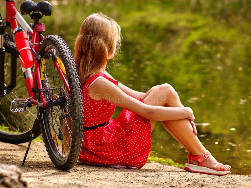 Ποδήλατα που ανακυκλώνουν το κορίτσι στο πάρκο Το κορίτσι κάθεται την κλίση στο ποδήλατο στην ακτή στοκ φωτογραφία με δικαίωμα ελεύθερης χρήσης