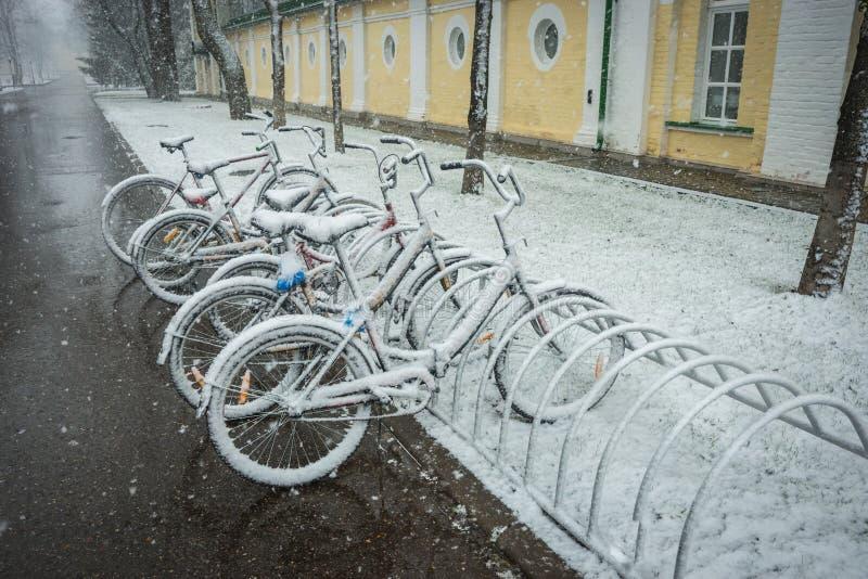 Ποδήλατα που καλύπτονται ομαλά με το φρέσκο χιόνι μετά από τα καιρικά φαινόμενα - χιονοπτώσεις τέλη Απριλίου κοντά στη Μόσχα στοκ φωτογραφίες