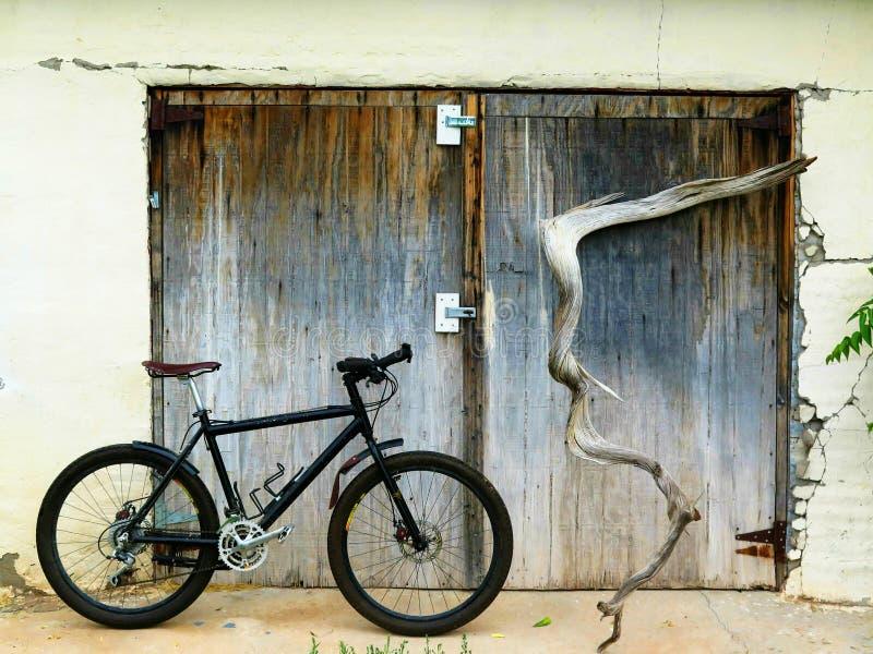 Ποδήλατο βουνών με τις ξεπερασμένες ξύλινες πόρτες στοκ εικόνες