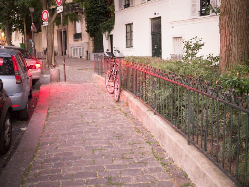 Ποδήλατο που κλίνει ενάντια στο φράκτη σιδήρου, που λούζεται στο κόκκινο φως από την κυκλοφορία, Montmartre, Παρίσι, στις αρχές β στοκ φωτογραφίες