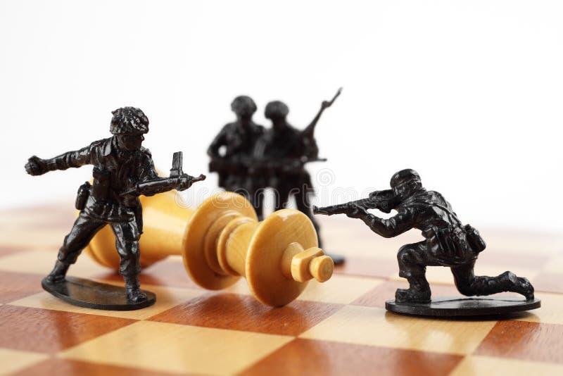 Πολεμική έννοια Οι στρατιώτες παιχνιδιών σκοτώνουν το βασιλιά σκακιού ο θάνατος σκακιού ματ λογαριάζει γίνοντη τη βασιλιάς χειρων στοκ εικόνα με δικαίωμα ελεύθερης χρήσης
