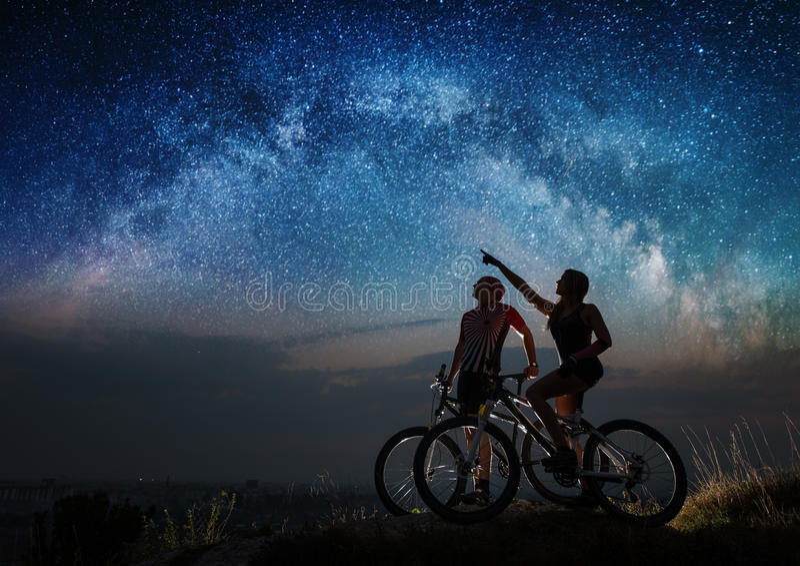 Ποδηλάτες ζεύγους με τα ποδήλατα βουνών τη νύχτα κάτω από τον έναστρο ουρανό στοκ εικόνες