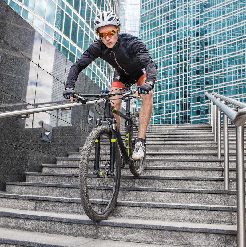 Ποδηλάτης αθλητικών τύπων στο ποδήλατο κάτω από τα σκαλοπάτια στο αστικό υπόβαθρο στοκ φωτογραφίες
