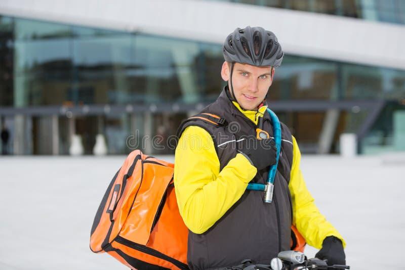 Ποδηλάτης με την τσάντα παράδοσης αγγελιαφόρων που χρησιμοποιεί Walkie- στοκ εικόνα με δικαίωμα ελεύθερης χρήσης