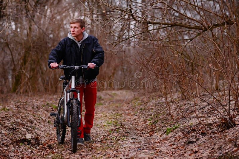 Ποδηλάτης που οδηγά ένα ποδήλατο βουνών κατά μήκος του δασικού δρόμου στοκ εικόνα