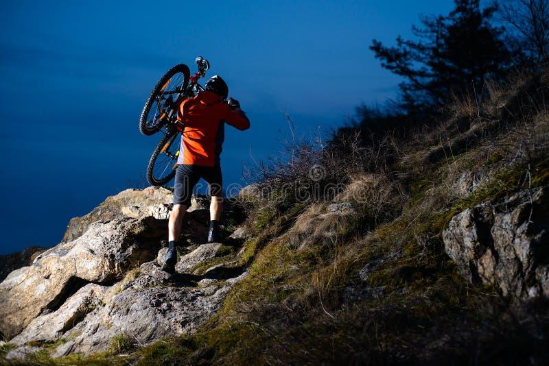 Ποδηλάτης Enduro που λαμβάνει το ποδήλατό του το δύσκολο ίχνος τη νύχτα Ακραία αθλητική έννοια Διάστημα για το κείμενο στοκ εικόνα