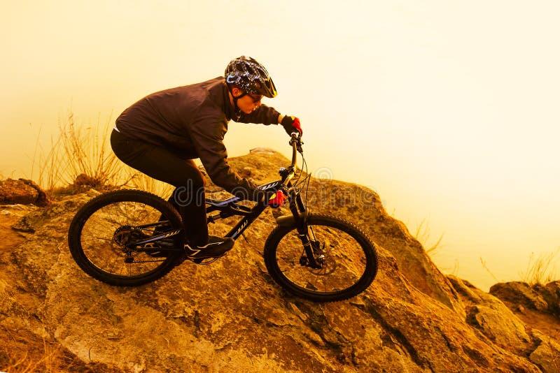 Ποδηλάτης Enduro που οδηγά το ποδήλατο βουνών στο βράχο Ακραία αθλητική έννοια Διάστημα για το κείμενο στοκ φωτογραφία με δικαίωμα ελεύθερης χρήσης