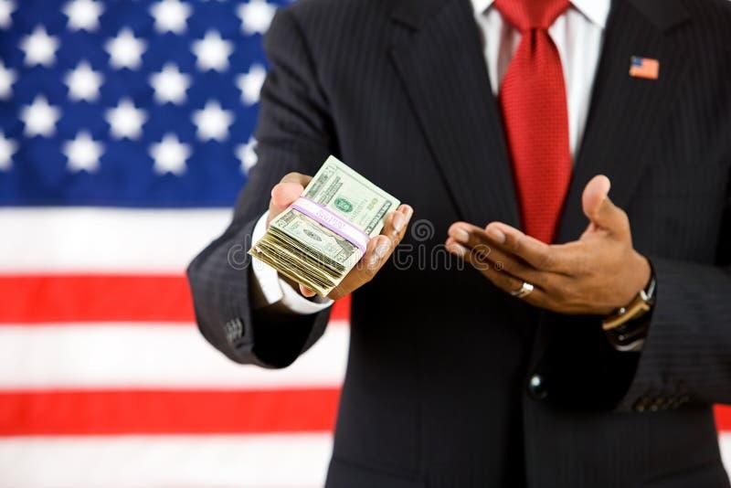 Πολιτικός: Ο πολιτικός παρουσιάζει σωρό χρημάτων στοκ εικόνες