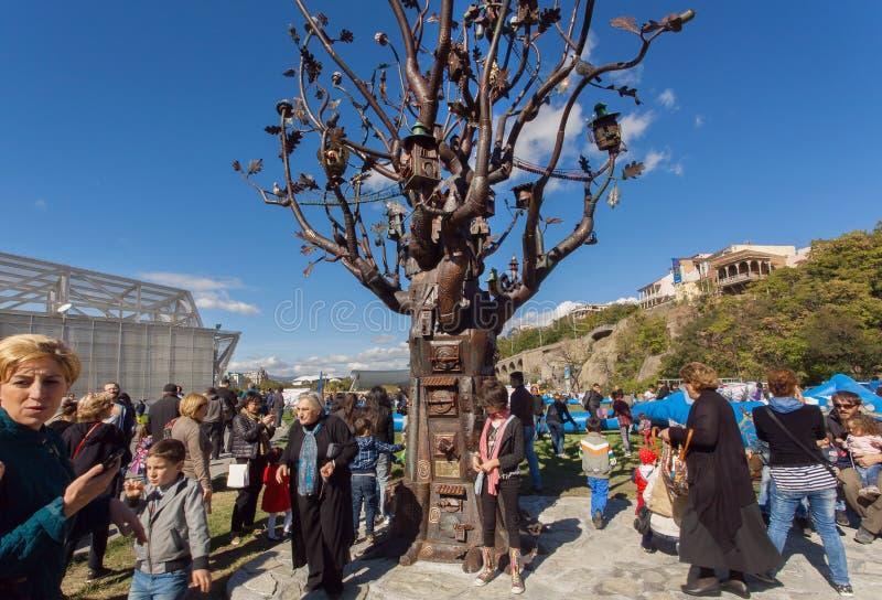 Πολλοί άνθρωποι με τις οικογένειες που περπατούν σε Rike σταθμεύουν με το δέντρο μετάλλων της ζωής στοκ εικόνες με δικαίωμα ελεύθερης χρήσης