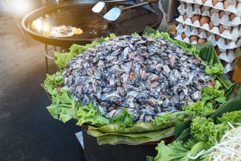 Πολλοί ακατέργαστο μύδι προετοιμάζονται γιατί ο μάγειρας είναι τηγανίτα μυδιών στοκ εικόνες