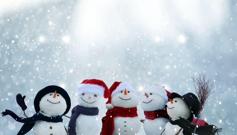 Πολλοί χιονάνθρωποι που στέκονται στο τοπίο χειμερινών Χριστουγέννων στοκ εικόνες
