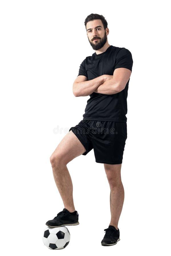 Ποδοσφαιριστής που στέκεται στη σφαίρα με τη μια τοποθέτηση ποδιών με τα διασχισμένα όπλα στοκ φωτογραφία με δικαίωμα ελεύθερης χρήσης