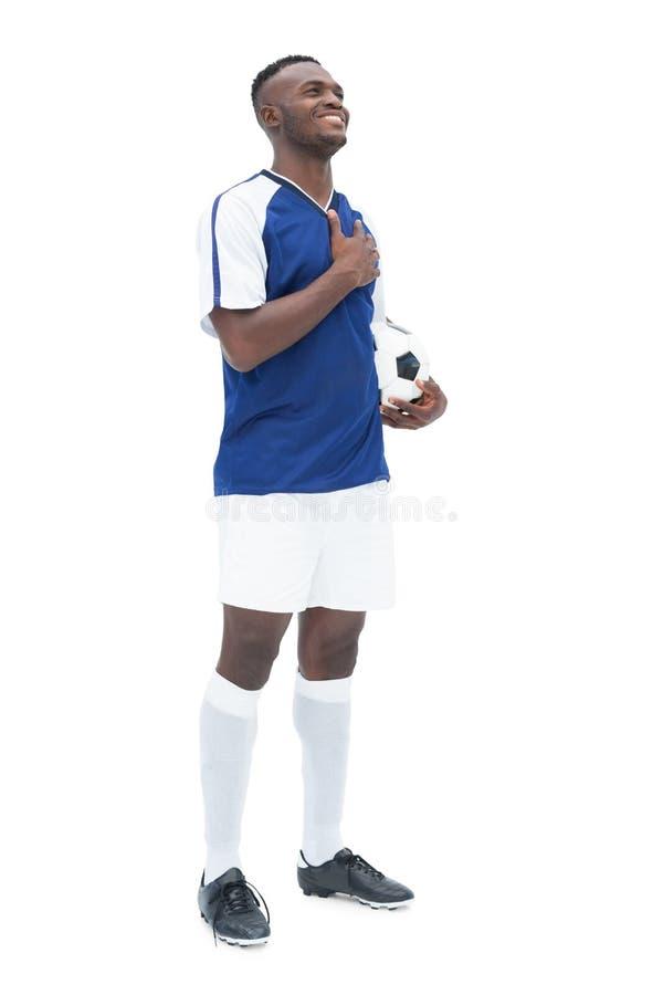 Ποδοσφαιριστής στην μπλε στάση με τη σφαίρα που ακούει τον ύμνο στοκ φωτογραφία με δικαίωμα ελεύθερης χρήσης