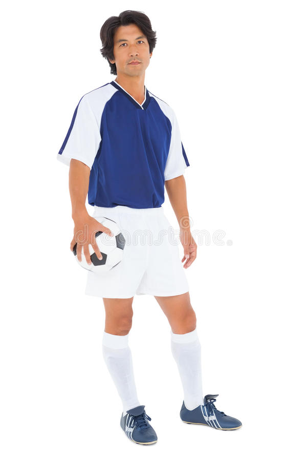 Ποδοσφαιριστής στην μπλε σφαίρα εκμετάλλευσης στοκ φωτογραφία με δικαίωμα ελεύθερης χρήσης