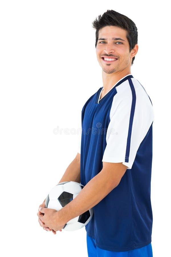 Ποδοσφαιριστής στην μπλε σφαίρα εκμετάλλευσης στοκ φωτογραφίες