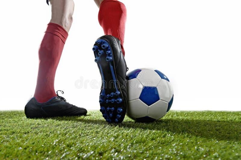 Ποδοσφαιριστής στις κόκκινες κάλτσες και τα μαύρα παπούτσια που τρέχουν και που στάζουν με το παιχνίδι σφαιρών στη χλόη στοκ φωτογραφία με δικαίωμα ελεύθερης χρήσης