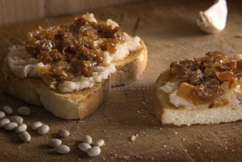 Πολτοποίηση φασόλια με τα τηγανισμένα κρεμμύδια στην κορυφή στοκ εικόνες