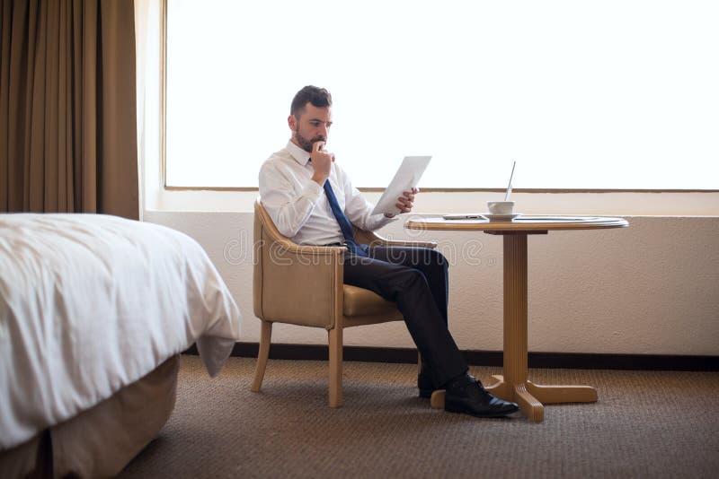 Πολυάσχολος αρσενικός δικηγόρος που εργάζεται στο δωμάτιο ξενοδοχείου του στοκ εικόνες
