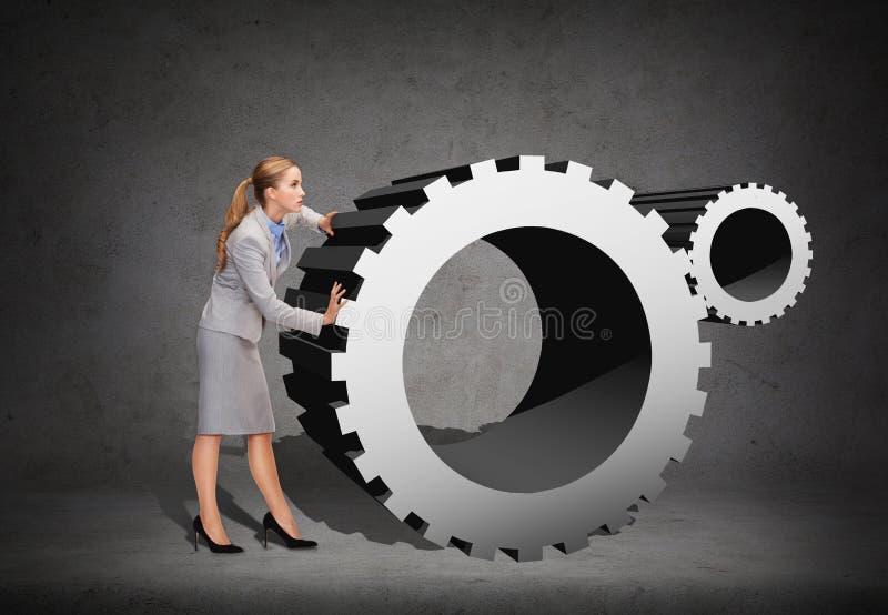Πολυάσχολο ωθώντας cogwheel επιχειρηματιών στοκ φωτογραφίες