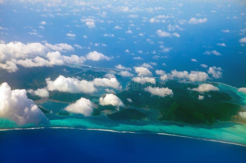 Πολυνησία. Η ατόλλη στον ωκεανό μέσω των σύννεφων. Τροπικό τοπίο θάλασσας σε μια ηλιόλουστη ημέρα στοκ εικόνα