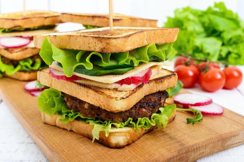 Πολυστρωματικά σάντουιτς με juicy cutlet, τυρί, ραδίκι, αγγούρι, μαρούλι, arugula στοκ φωτογραφία
