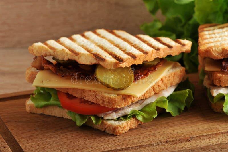 Πολυστρωματικό σάντουιτς με το τυρί, το ζαμπόν, τις ντομάτες, τα τουρσιά και το LE στοκ εικόνες