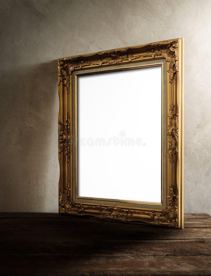 Πολυτελές πλαίσιο φωτογραφιών στον ξύλινο πίνακα πέρα από το υπόβαθρο grunge στοκ εικόνες