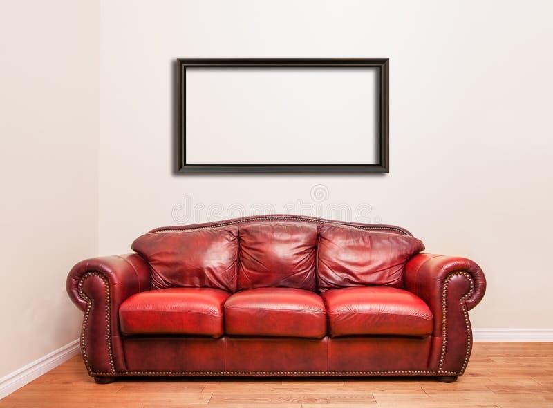Πολυτελής κόκκινος καναπές δέρματος μπροστά από έναν κενό τοίχο στοκ εικόνες με δικαίωμα ελεύθερης χρήσης