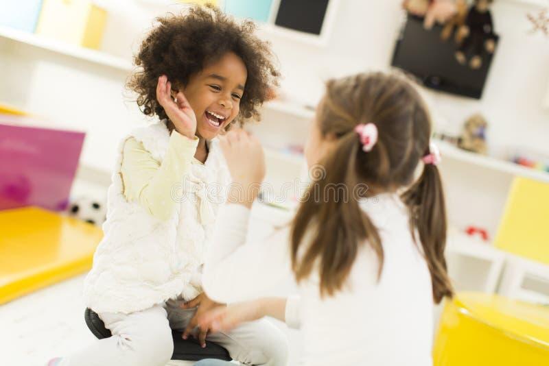 Πολυφυλετικά κορίτσια liitle στο χώρο για παιχνίδη στοκ εικόνα με δικαίωμα ελεύθερης χρήσης