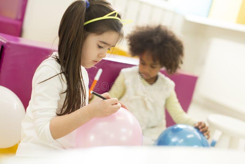 Πολυφυλετικά κορίτσια liitle στο χώρο για παιχνίδη στοκ εικόνες
